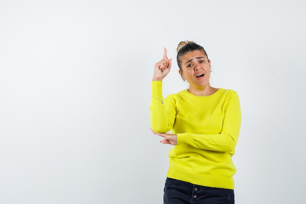 Young woman in yellow sweater and black pants raising index finger in eureka gesture while holding hand on elbow and looking sensible