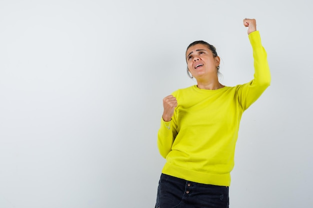 Young woman in yellow sweater and black pants showing winner gesture and looking happy