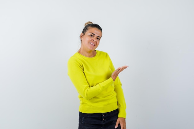 Young woman in yellow sweater and black pants stretching hand toward right and looking happy
