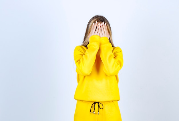 Young woman in yellow sweatsuit covering her face over white wall