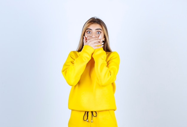 Young woman in yellow sweatsuit covering her mouth over white wall