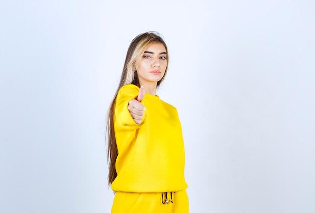 Giovane donna in tuta gialla in posa per la telecamera su muro bianco
