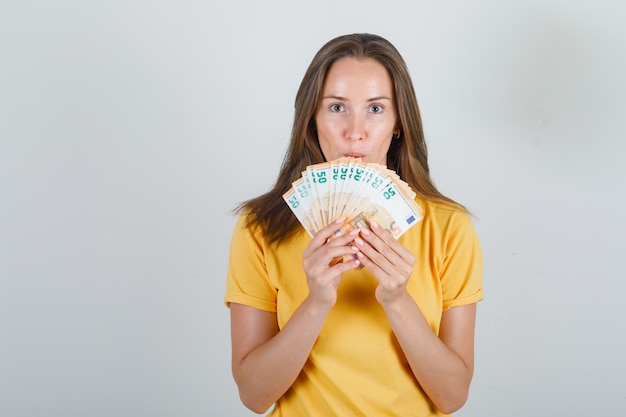 Young woman in yellow t-shirt, holding euro banknotes and looking careful