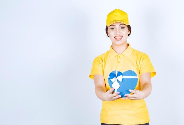 Giovane donna nella scatola gialla unishape che tiene la scatola a forma di cuore su un muro bianco