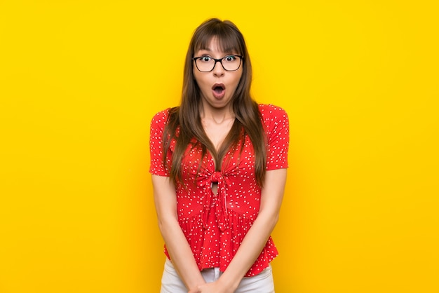 Young woman over yellow wall with surprise facial expression