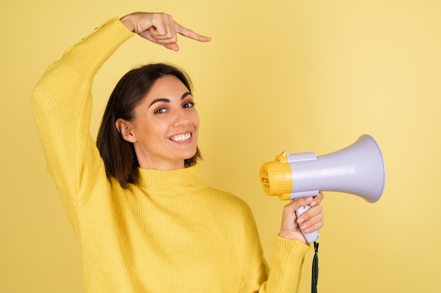 Young woman in yellow warm sweater with megaphone speaker and pointing finger to right