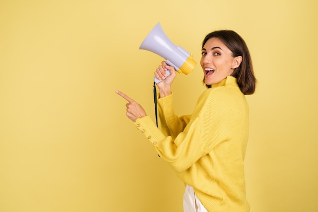Young woman in yellow warm sweater with megaphone speaker screaming to the left pointing index finger
