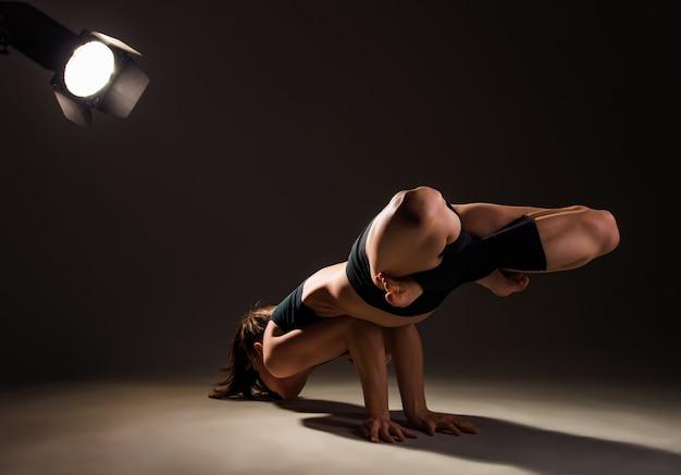 暗い照明のスタジオでレーザーを使って手で複雑なアーサナをやっている若い女性のヨガの先生