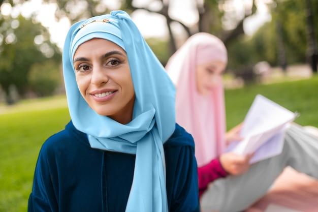 젊은 여성. 광범위 하 게 웃 고 주황색 태블릿을 들고 밝은 파란색 hijab를 착용하는 젊은 여자