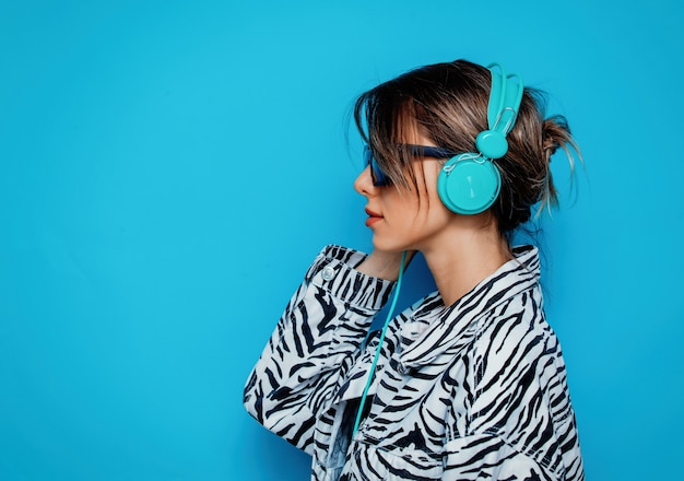 Young woman in zebra clothes and headphones on blue background
