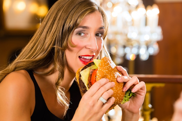 Young womana fine dining restaurant eat a hamburger, she behaves improperly