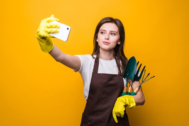 Young womang ardener take selfie on the phone while holding tools isolated