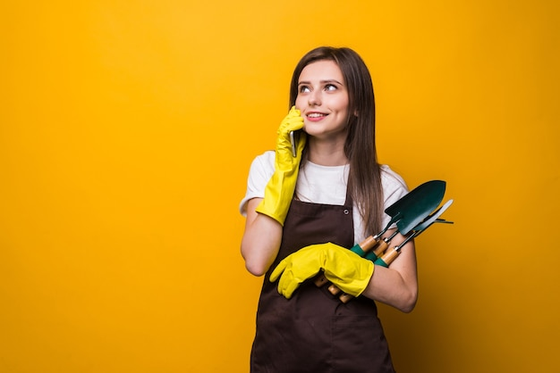Young womang ardener talking on the phone while holding tools isolated Free Photo