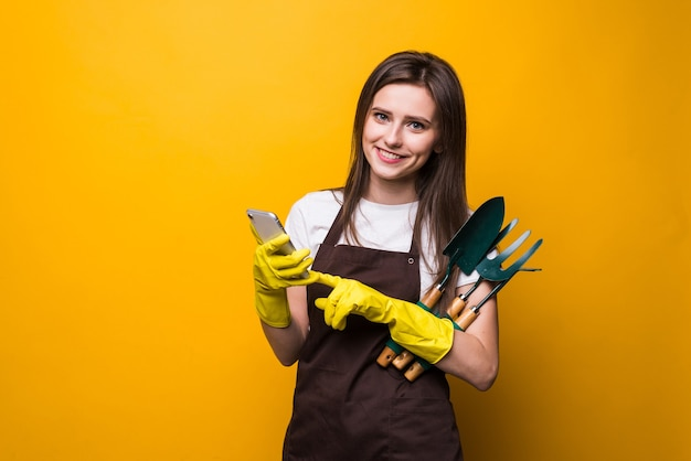 Young womang ardener typing on the phone while holding tools isolated