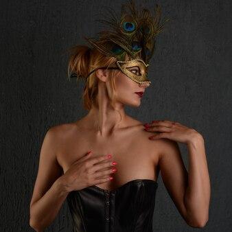 젊은 Womanin 베네치아 카니발 마스크 클로즈업 여성 초상화입니다. 어두운 배경 프리미엄 사진