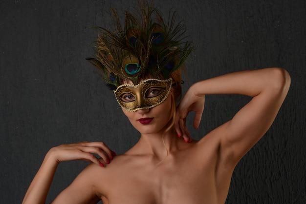 若い女性のベネチアンカーニバルマスククローズアップ女性の肖像画。暗い背景