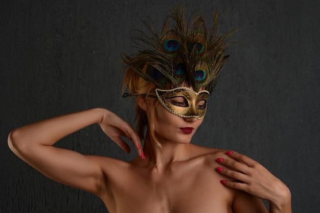 젊은 womanin 베네치아 카니발 마스크 클로즈업 여성 초상화입니다. 어두운 배경