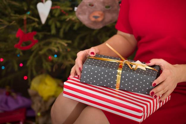 아름답게 포장된 크리스마스 생일이나 다른 축하 선물을 든 젊은 여성의 손