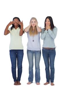 Молодые женщины, выступающие за трех мудрых обезьян
