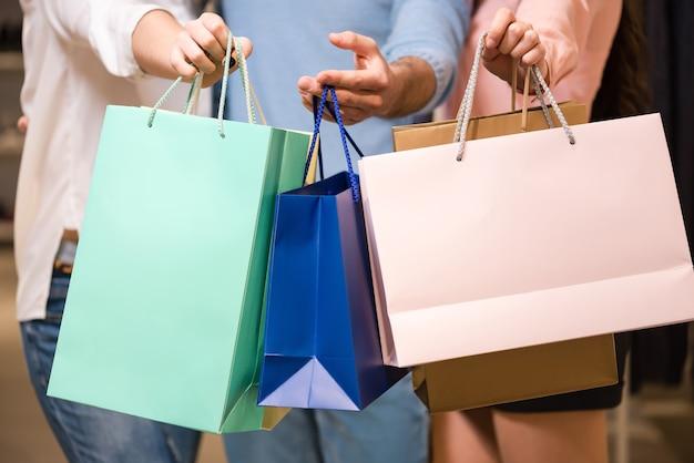 色とりどりの紙の買い物袋を持つ若い女性と男性、クローズアップ