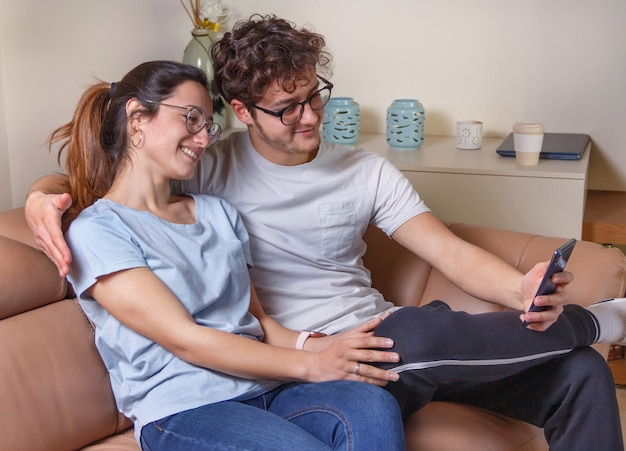 Молодые женщины и мужчины могут вести видеозвонок по мобильному телефону, сидя на бежевом диване у себя дома. молодой мужчина держит в руке смартфон.