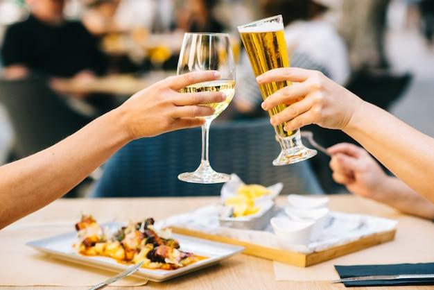 Молодые женщины аплодируют пиву и едят на террасе - две девушки вместе обедают в ресторане