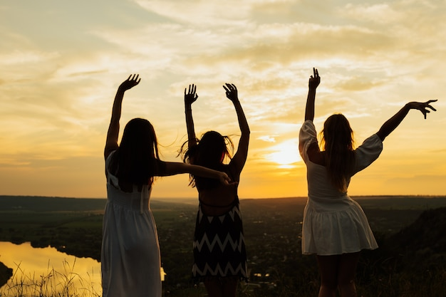 Young women are having fun on the mountain in the evening at perfect sunset.