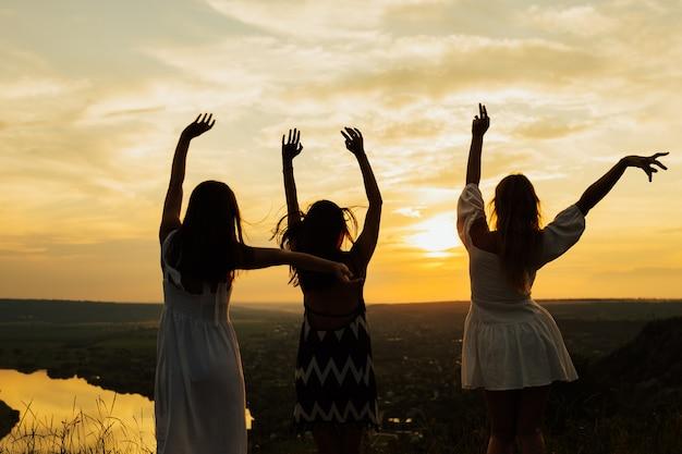 若い女性は完璧な日没の夕方に山で楽しんでいます。