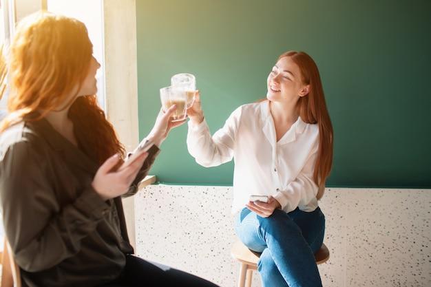 Молодые женщины разговаривают в кафе. женские модели пьют кофе и улыбаются.
