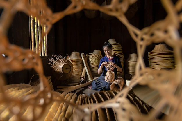 Young women are weaving in field handmade basket of thailand.