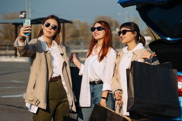 買い物袋が付いている車で若い女性。女の子は自分撮りを取る