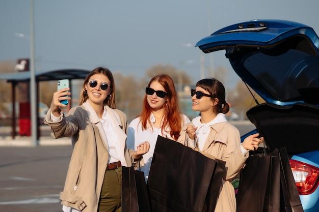 쇼핑 가방과 함께 차에 젊은 여성. 셀카 찍는 여자