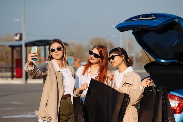 Selfi를 만드는 쇼핑백과 차에서 젊은 여성