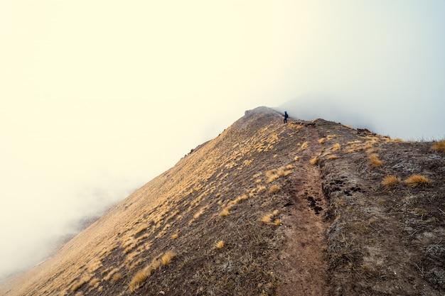 山の上に霧を探している若い女性バックパッカー