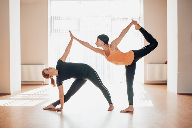 Young women balancing and practicing yoga in a light studio