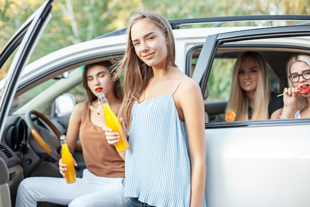 Le giovani donne in macchina sorridono e bevono succo