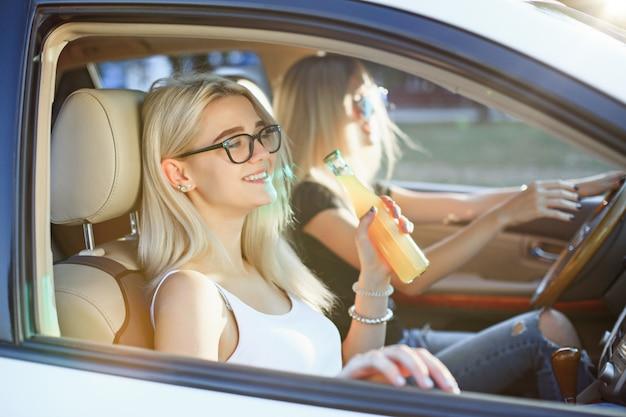 Le giovani donne in macchina sorridono