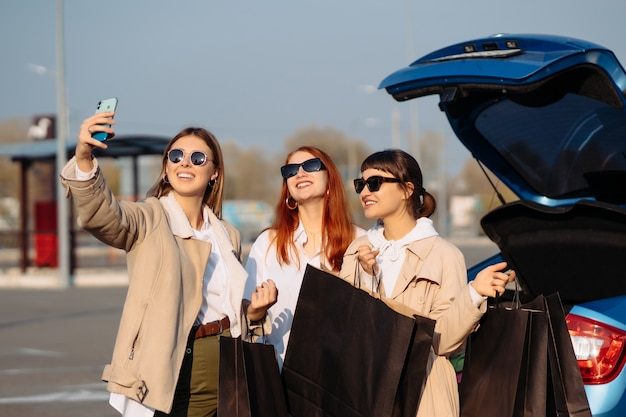 Young women at the car with shopping bags. girls take selfie
