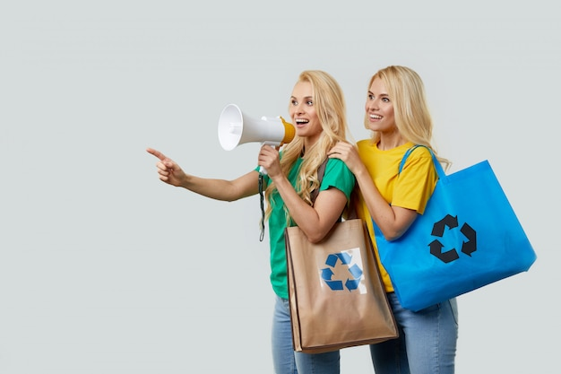 Young women in casual clothes are holding ecological recycled grocery bags and shouting into a megaphone to recycle plastic waste. point left to empty space for text.