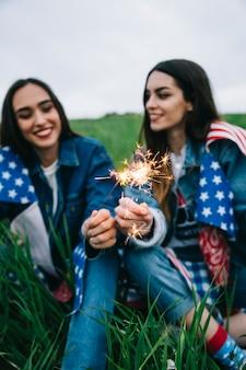 Молодые женщины празднуют 4 июля в поле