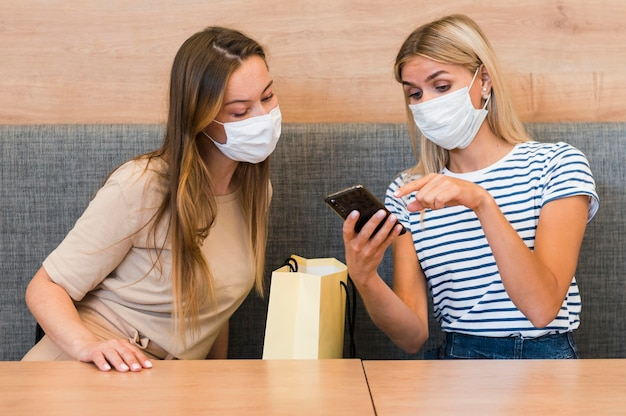若い女性が一緒に携帯電話をチェック