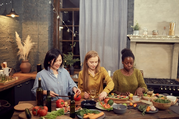 Young women cooking dinner for party