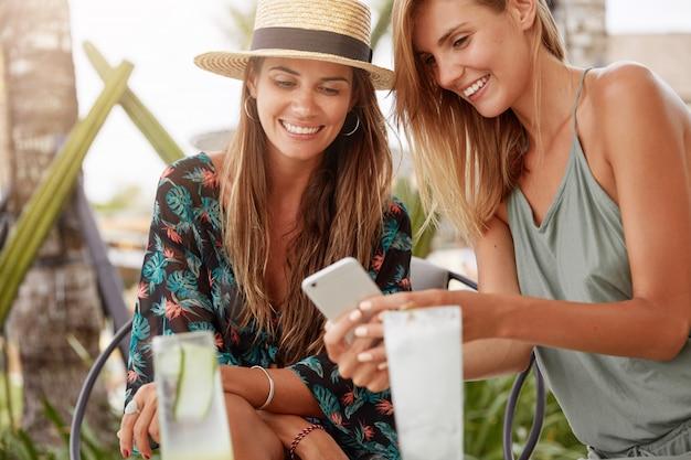 Пара молодых женщин вместе отдыхает в летнем кафе, радостно смотрит в смартфон