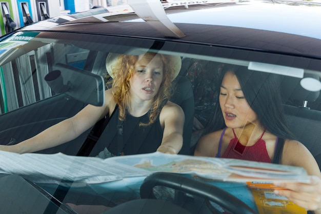 Young women discussing way in car