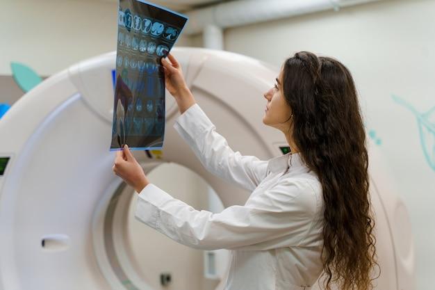 医療用ガウンの若い女性医師がctスキャナーの横にある結果を見る