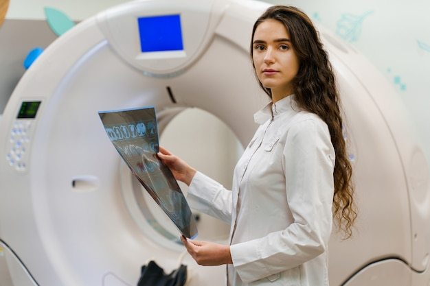 Young women doctor in medical gown looks at results next to ct scanner