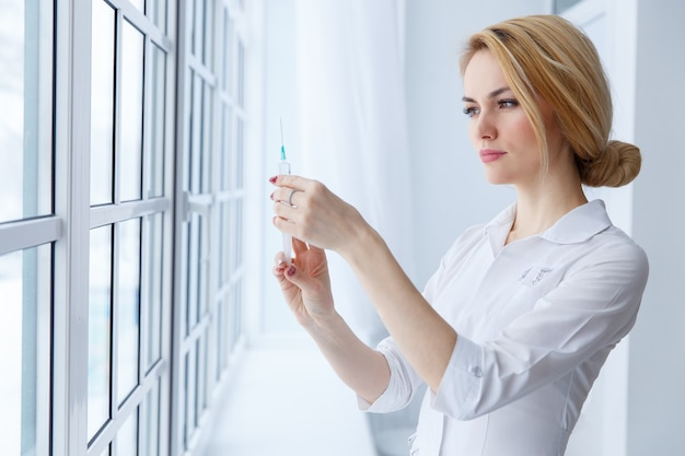 Young women doctor with syringe. medicine and health care concept.