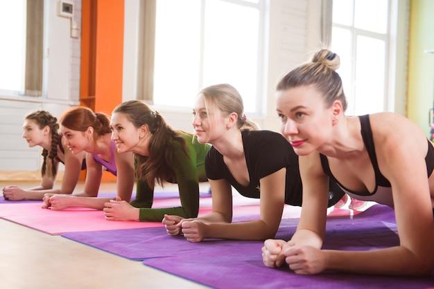 복부 운동을하는 젊은 여성. 연속으로 복근을하는 체육 수업.