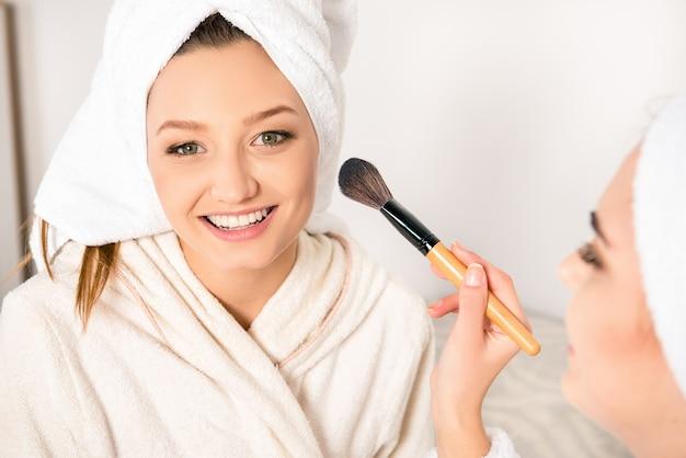 頭にタオルで化粧をしている若い女性