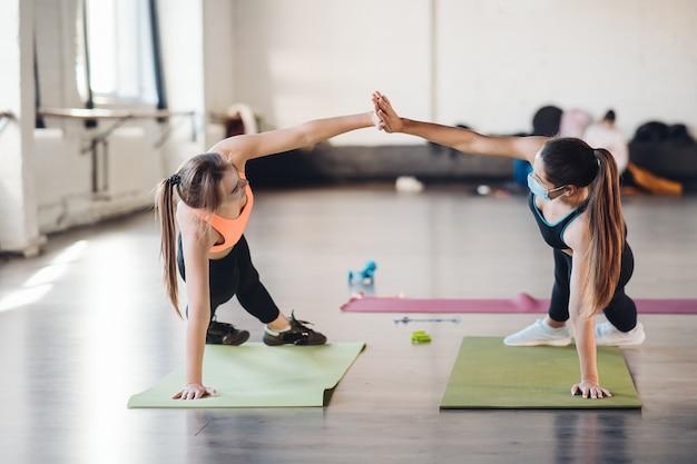 Le giovani donne che fanno spingere verso l'alto esercizio in camera durante la mattina